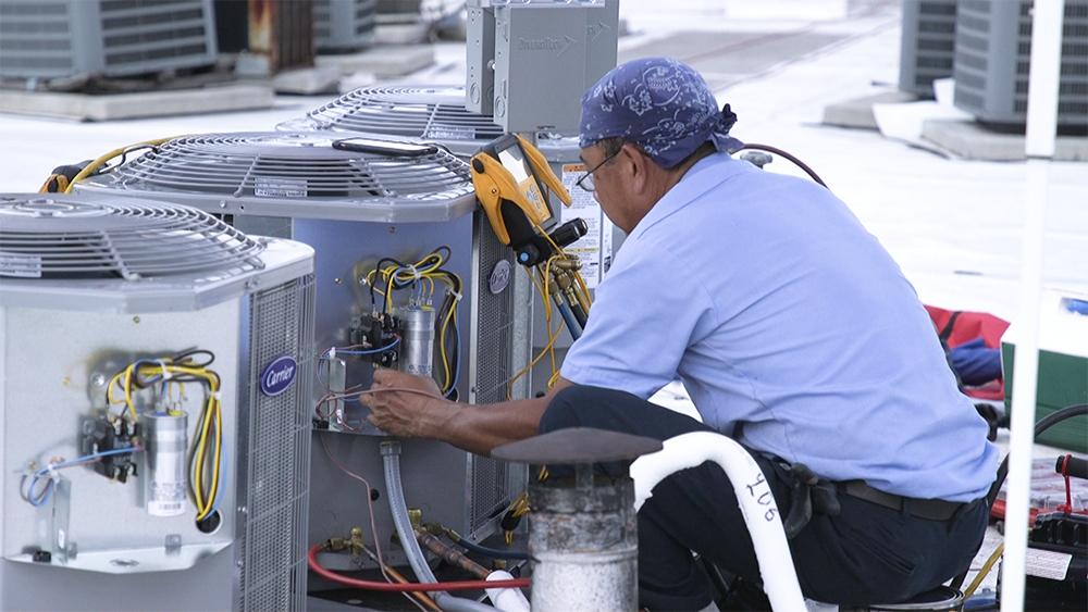 HVAC technician working on a multi-family job.