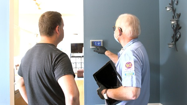 A technician explaining how to use a thermostat.