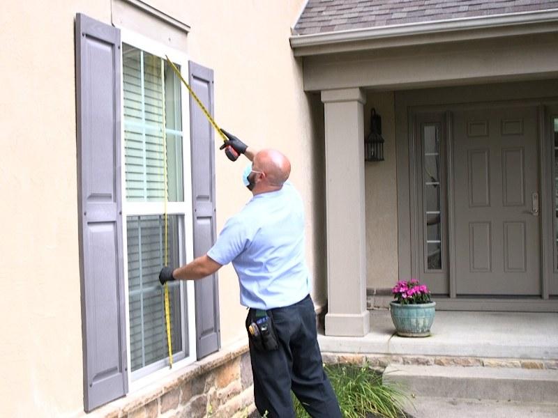A technician measuring a window.
