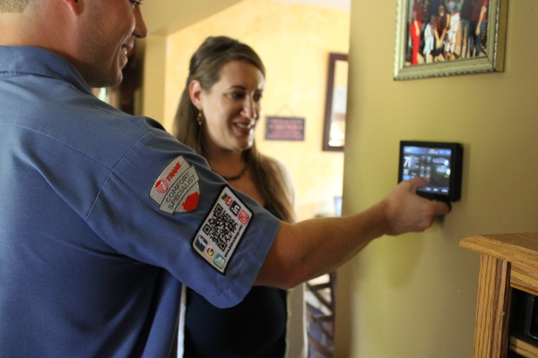 A technician showing a customer how to use their thermostat.