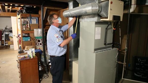 A technician measuring a furnace.