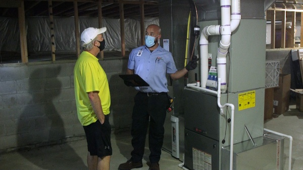 A technician speaking with a customer in their basement.