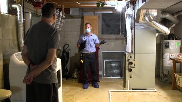 A technician explaining how a furnace works to a customer.