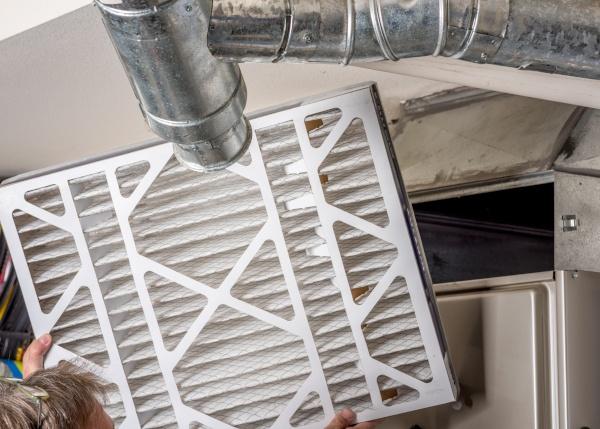 A technician replacing a furnace filter.