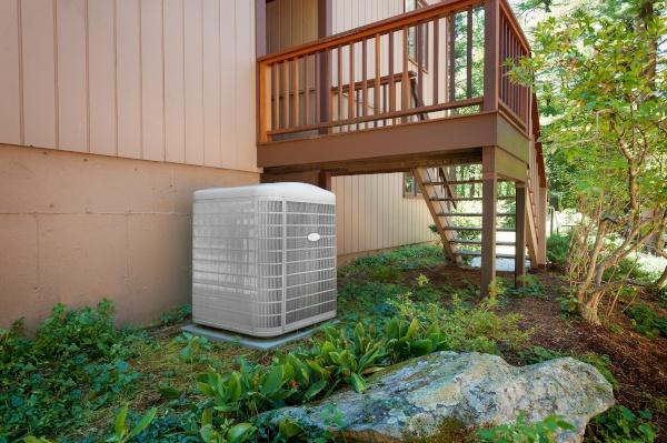 An HVAC unit near a porch.